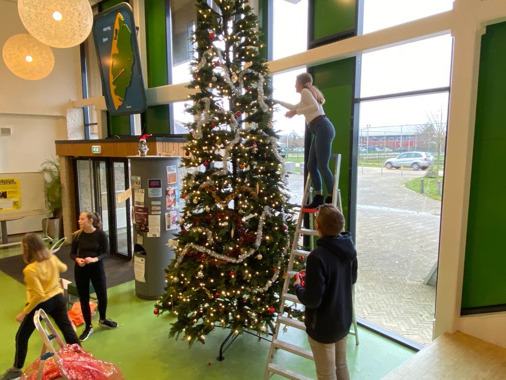 Leerlingen versieren kerstboom